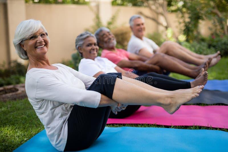 Gente mayor sonriente que ejercita con los pies para arriba fotografía de archivo