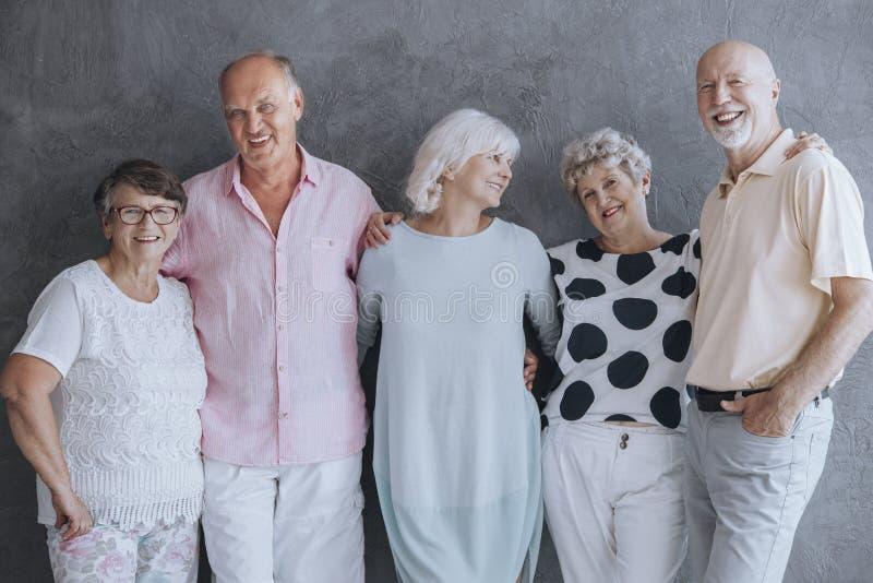 Gente mayor sonriente que se divierte, oponiéndose al muro de cemento imagen de archivo