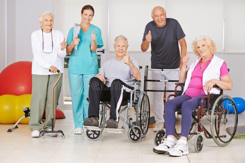 Gente mayor y enfermera que detienen los pulgares foto de archivo