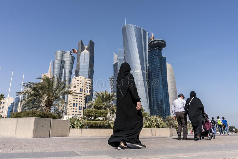 Gente media árabe de Pascua que camina en Corniche Broadway y que mira en la opinión del horizonte de Doha Qatar, Oriente Medio fotos de archivo