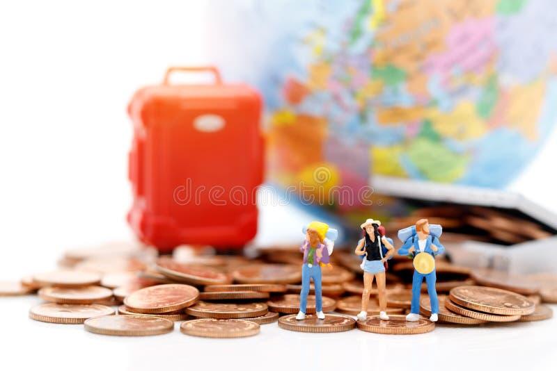 Gente miniatura, backpackers que se colocan en la pila de monedas fotos de archivo libres de regalías