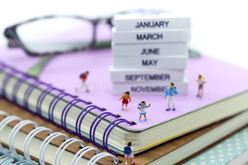 Gente miniatura: bambini e studente con il libro, stazionario immagine stock
