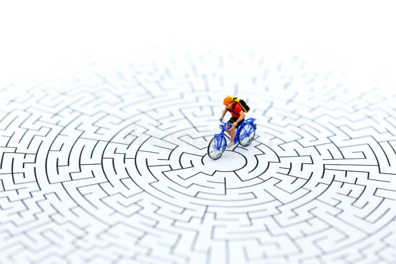 Gente miniatura: bicicleta del montar a caballo en el punto del comienzo del laberinto usando a imagen de archivo