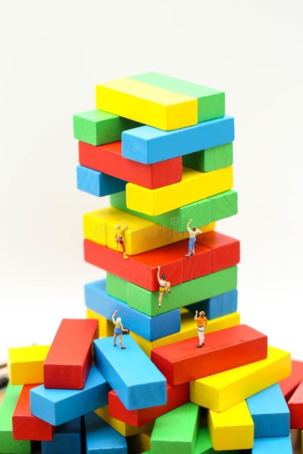 Gente miniatura: bloque de madera colorido que sube con challengi imagen de archivo
