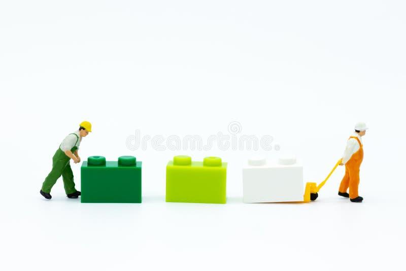 Gente miniatura: Camión de plataforma del uso del trabajador con las cajas coloridas Uso de la imagen para el negocio del fondo d fotos de archivo