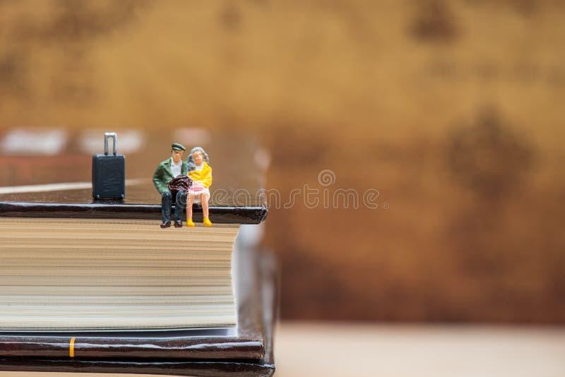 Gente miniatura che si siede sull'angolo del libro fotografia stock