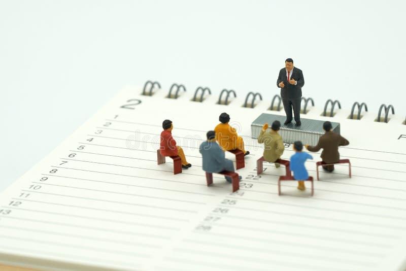 Gente miniatura che si siede sulle graffette di rosso disposte su una riunione o su una discussione della lista di posti del libr fotografia stock libera da diritti
