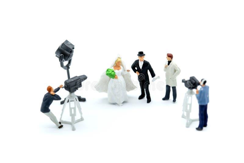 Gente miniatura: cineoperatore, Videographer alla fucilazione del lavoro sopra fotografia stock