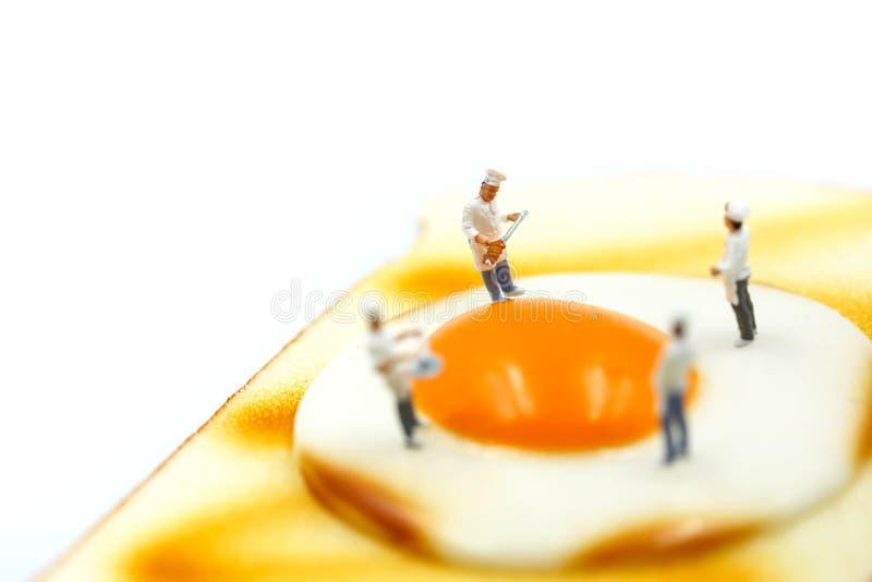 Gente miniatura: Cocinero en el pan de la tostada con el huevo en el backgro blanco imagen de archivo