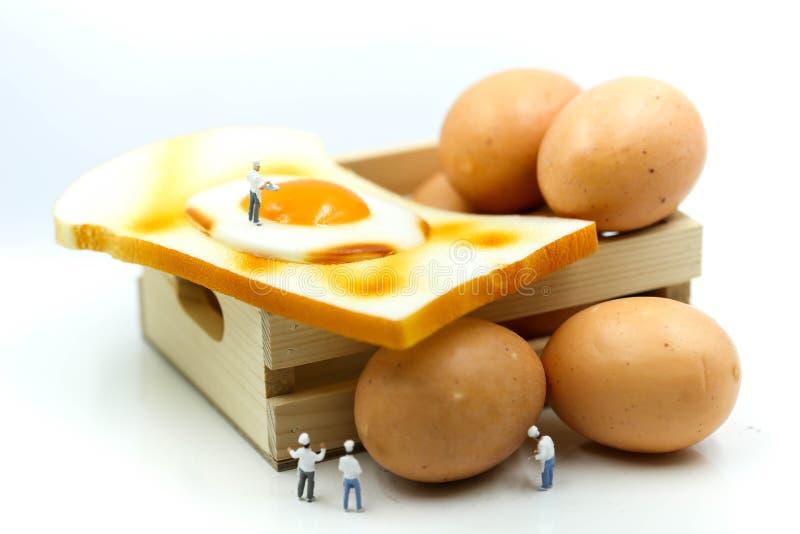 Gente miniatura: Cocinero que cocina con los huevos para el desayuno con el toa fotos de archivo libres de regalías
