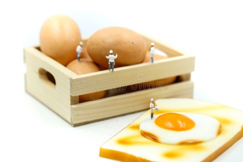 Gente miniatura: Cocinero que cocina con los huevos para el desayuno con el toa imagen de archivo