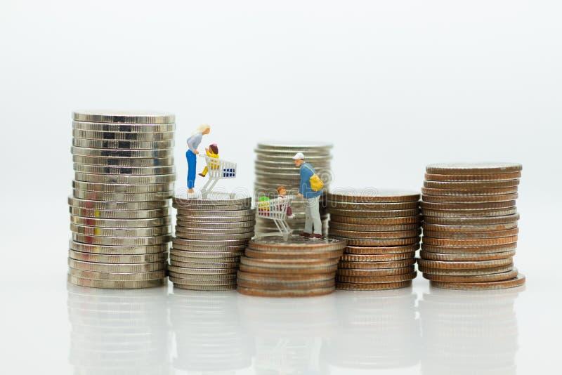 Gente miniatura, comprador con los niños que se sientan en el carro y soporte en la pila de monedas, gastar dinero para las merca foto de archivo libre de regalías
