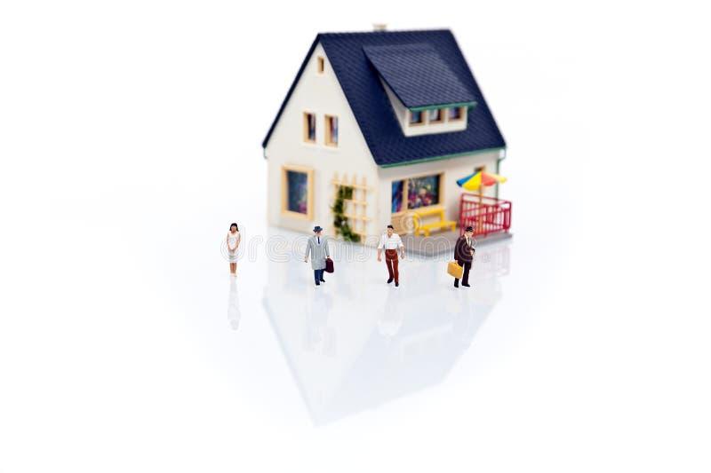 Gente miniatura con la casa fotografía de archivo