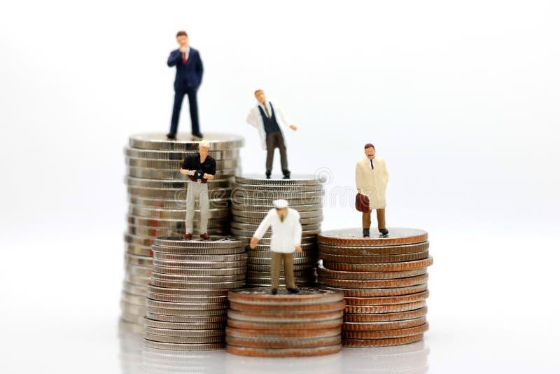Gente miniatura con los diversos empleos que se colocan en el dinero de las monedas imágenes de archivo libres de regalías