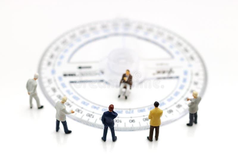 Gente miniatura: Condizione del gruppo di affari intorno al righello del cerchio fotografia stock
