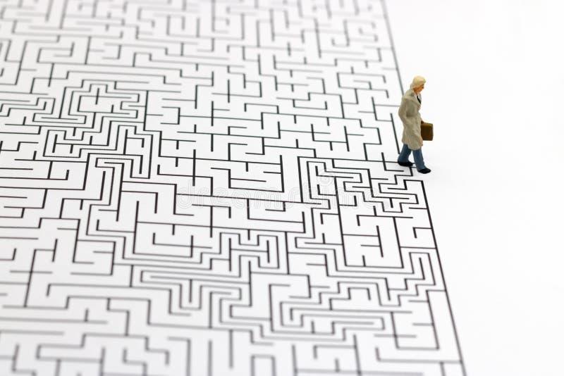 Gente miniatura: Condizione dell'uomo d'affari sul rivestimento di labirinto Concetti di individuazione della soluzione, di soluz fotografia stock libera da diritti