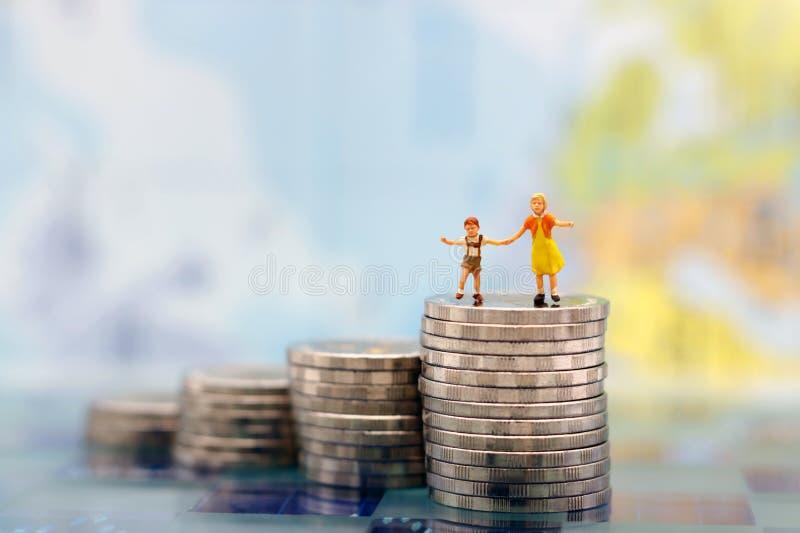 Gente miniatura: Coppie felici dei bambini che stanno sulla pila delle monete, fotografia stock