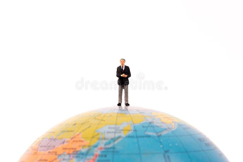 Gente miniatura del negocio que se coloca en el globo imagenes de archivo