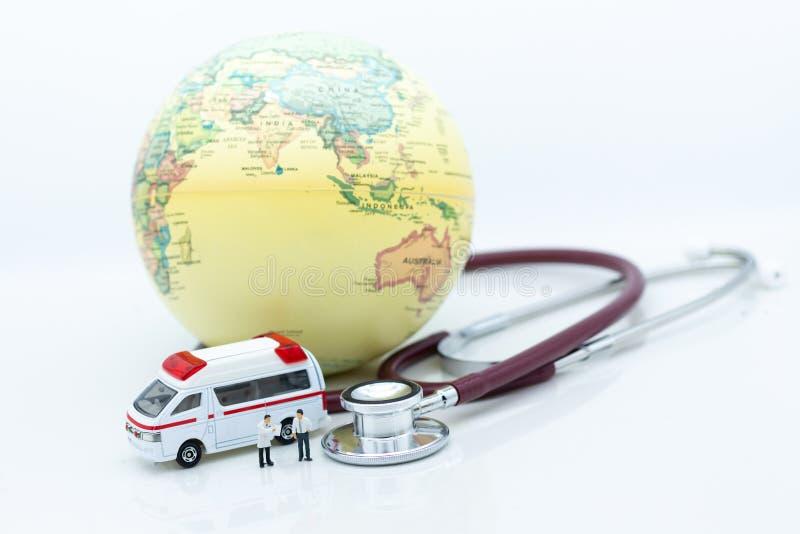 Gente miniatura, doctor con el estetoscopio y el mapa del mundo, ambulancia Uso de la imagen para la asistencia médica de la salu foto de archivo libre de regalías