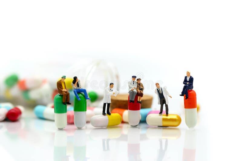 Gente miniatura: doctor y soporte paciente con la droga, píldoras, capsu imágenes de archivo libres de regalías