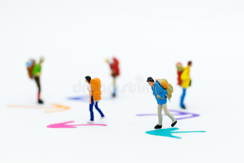 Gente miniatura: El caminar del grupo del Backpacker sigue la flecha Uso de la imagen para el viaje, concepto del negocio fotografía de archivo
