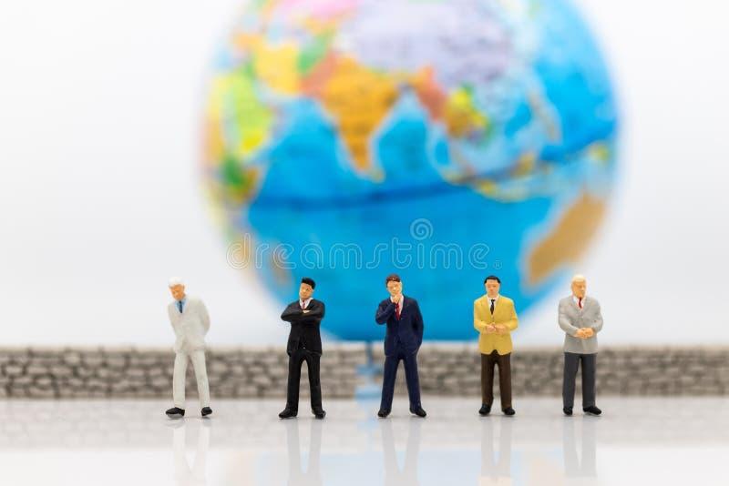 Gente miniatura: El frente de la situación del hombre de negocios de la pared y del mundo es interior El uso de la imagen para el foto de archivo