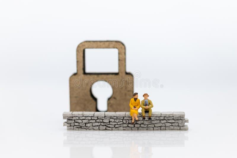 Gente miniatura: El hombre de negocios que se sienta en la pared y tiene llave principal es interior El uso de la imagen para el  imagen de archivo