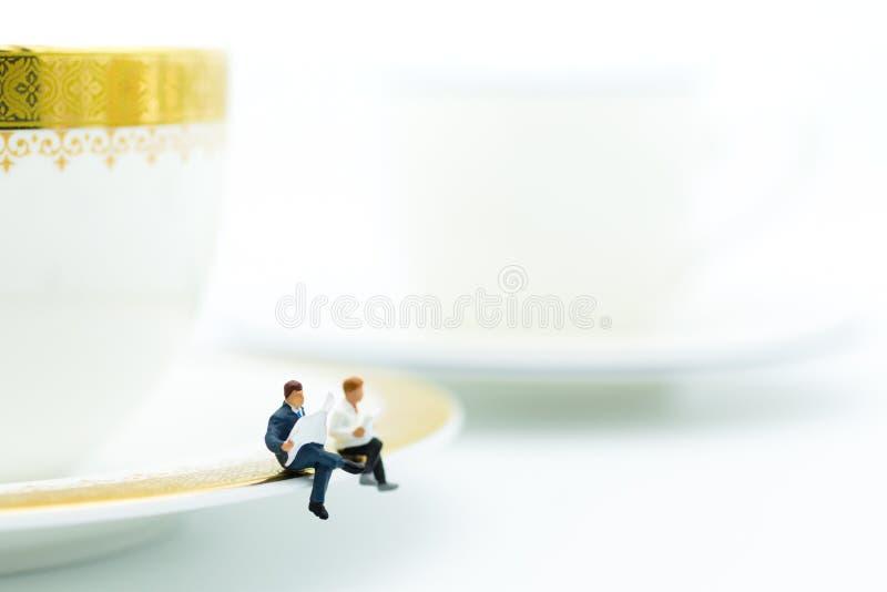 Gente miniatura: El hombre de negocios que se sienta en la taza de café y tiene papel de las noticias de la lectura Uso de la ima imagen de archivo libre de regalías