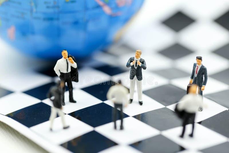 Gente miniatura: entrenamiento de la estrategia del equipo del negocio con concepto del ajedrez, de la blanco, de la decisión y d fotos de archivo libres de regalías