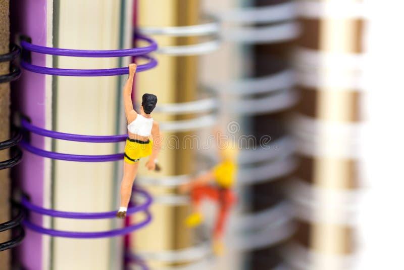Gente miniatura: Escalador que sube en el libro Uso de la imagen para aprender, concepto de la educación imagen de archivo