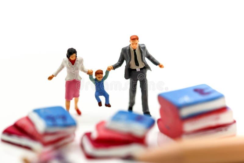 Gente miniatura: familia que lleva a cabo la mano con los libros Educación concentrada foto de archivo