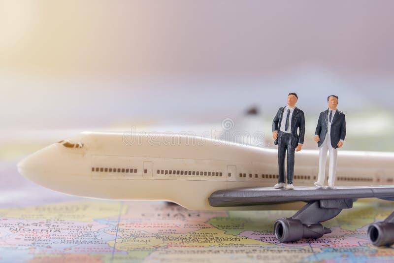 Gente miniatura - figure los businessmans que se colocan en airplan blanco imagen de archivo
