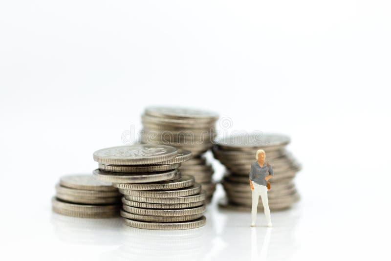 Gente miniatura: Gente finanziaria che sta sulle monete L'uso di immagine per il concetto di contabilità di affari, controlla l'i immagine stock libera da diritti