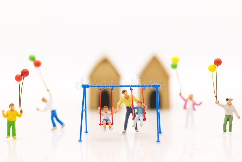 Gente miniatura: generi la culla dell'oscillazione con i bambini ed il pallone del gioco dei bambini insieme a divertimento fotografia stock