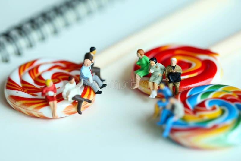 Gente miniatura: Giornale e seduta della lettura dell'uomo d'affari sulla c immagine stock