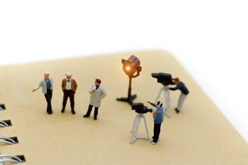 Gente miniatura: giornalista femminile che rende ad un'intervista un uomo fotografie stock