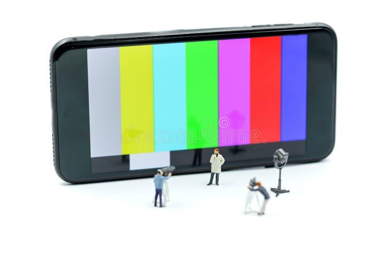 Gente miniatura: giornalisti, cineoperatore, Videographer sul lavoro immagini stock libere da diritti