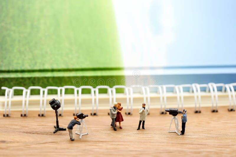 Gente miniatura: giornalisti, cineoperatore, Videographer sul lavoro fotografia stock libera da diritti