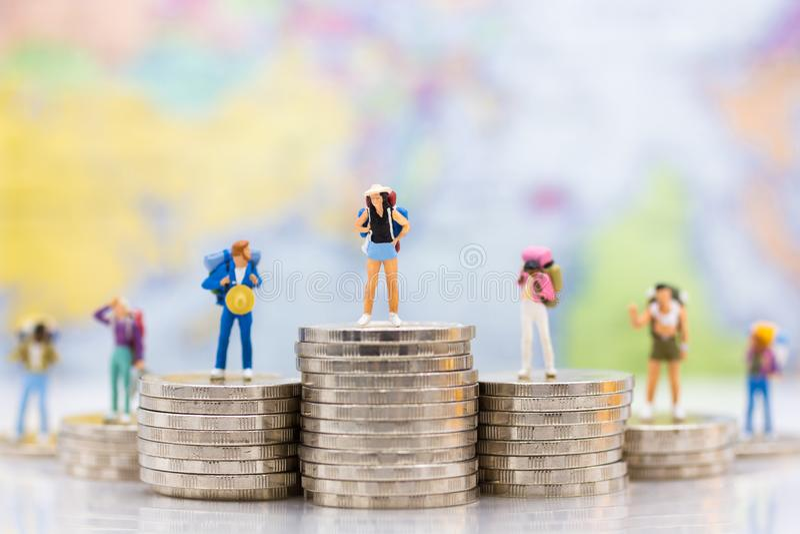 Gente miniatura: Grupo del Backpacker que se coloca en la pila de monedas Uso de la imagen para el viaje, concepto del negocio foto de archivo