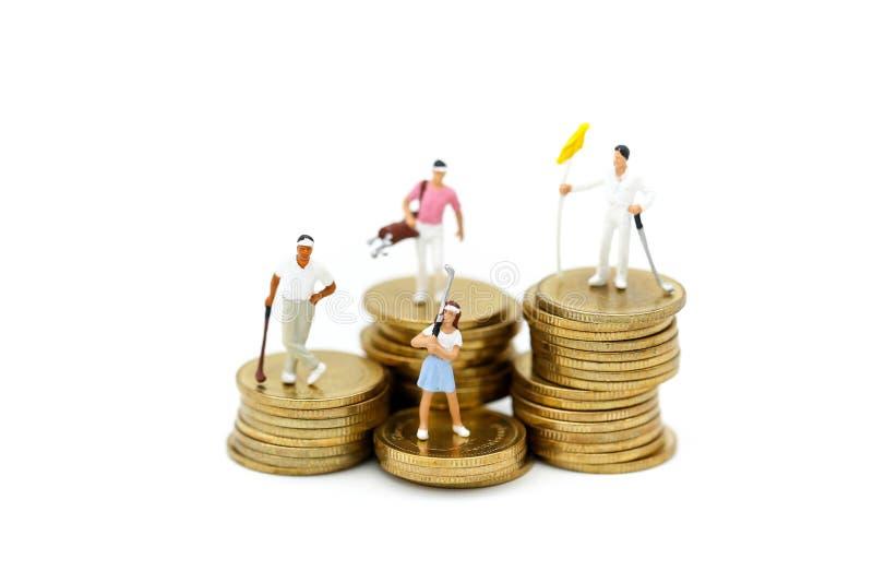 Gente miniatura: Gruppi del giocatore di golf che giocano supporto con la pila di moneta immagini stock libere da diritti
