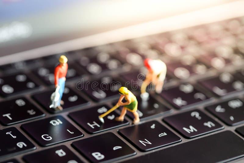 Gente miniatura: gruppo del lavoratore con il bottone su un keyboa del computer immagini stock