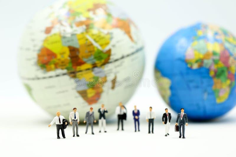Gente miniatura: Gruppo dell'uomo d'affari con miniworld, concetto internazionale di affari immagini stock