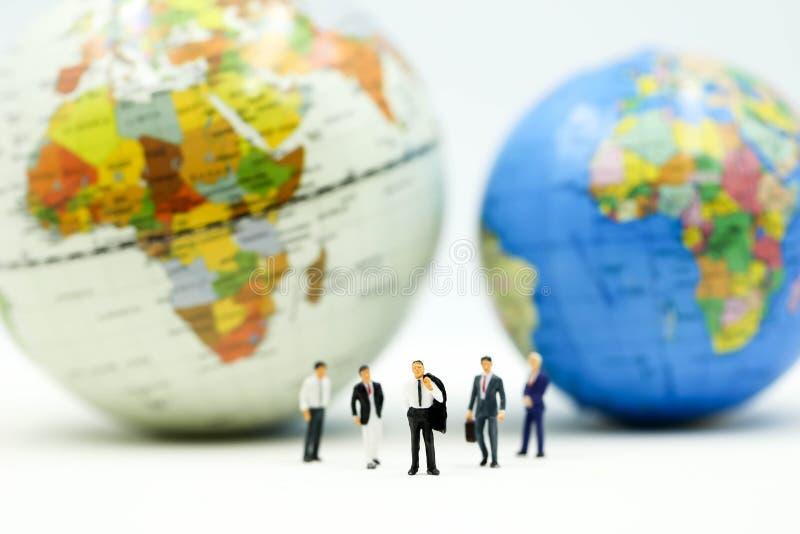 Gente miniatura: Gruppo dell'uomo d'affari con miniworld, concetto internazionale di affari fotografie stock