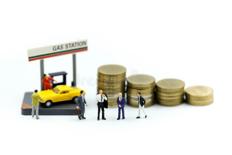 Gente miniatura: Hombre de negocios On Gas Station con las monedas, negocio imagen de archivo libre de regalías