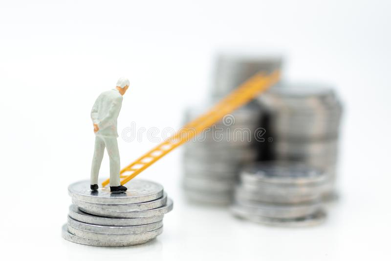 Gente miniatura: Hombre de negocios que piensa y que se coloca en la pila de monedas con la escalera Uso de la imagen para el cre imagen de archivo libre de regalías