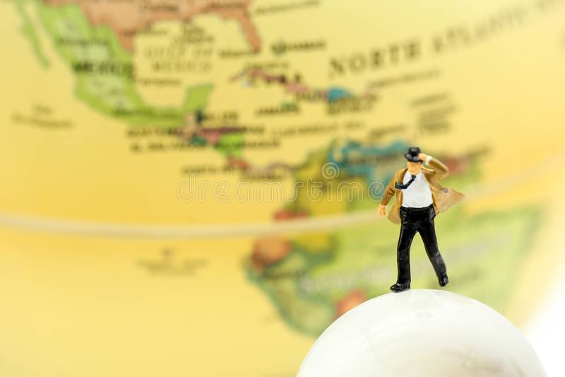 Gente miniatura: hombre de negocios que se coloca con el mapa del mundo, negocio foto de archivo libre de regalías