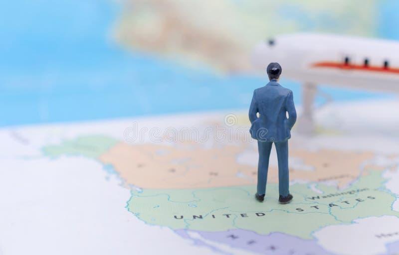 Gente miniatura, hombre de negocios que se coloca en americano del mapa fotos de archivo