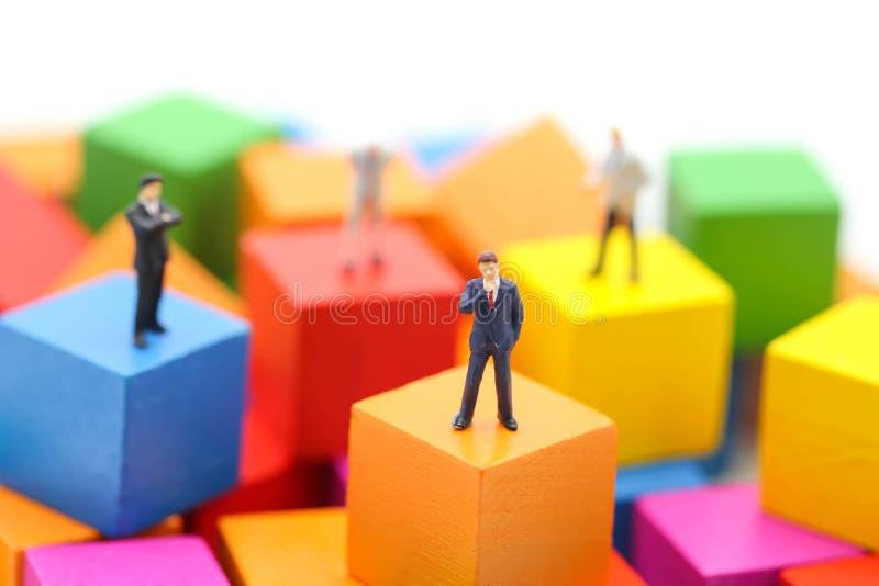 Gente miniatura: hombre de negocios que se coloca en el bloque de madera del color, usi foto de archivo libre de regalías