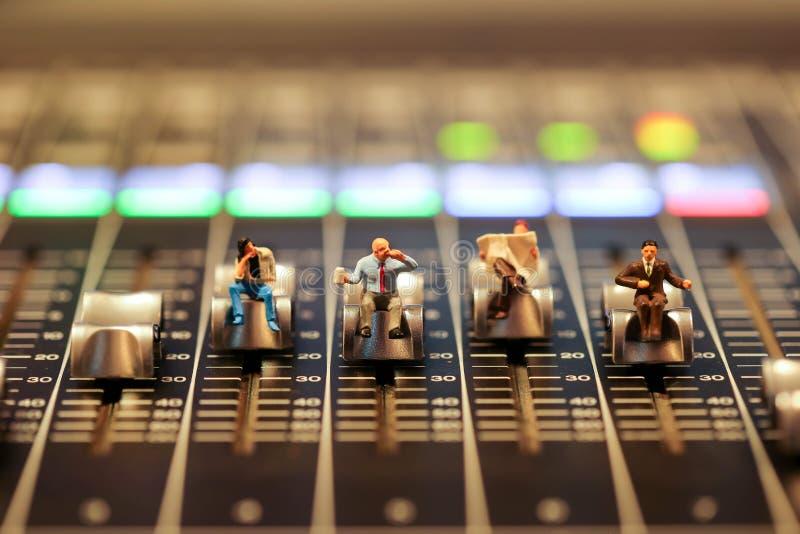 Gente miniatura: hombre de negocios que se sienta en el audio profesional MI imágenes de archivo libres de regalías