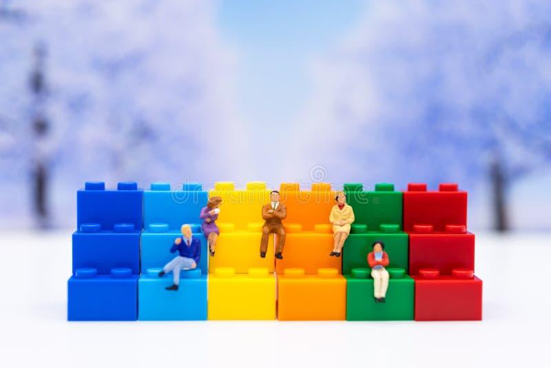 Gente miniatura: Hombre de negocios que se sienta en los gráficos, márgenes de beneficio del fondo Uso de la imagen para el conce imagenes de archivo